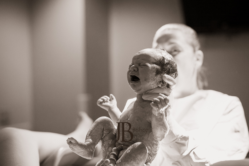 first photo of new baby being born birth photography