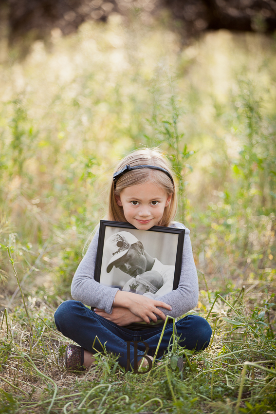 little girl hugging picture of daddy