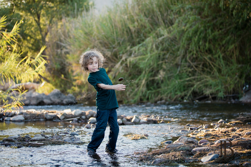 young boy playing in the river